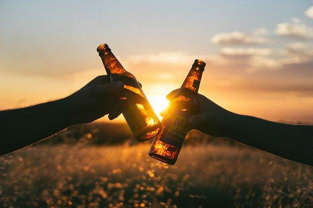 Ruce držící k přípitku lahve s pivem, v pozadí západ slunce